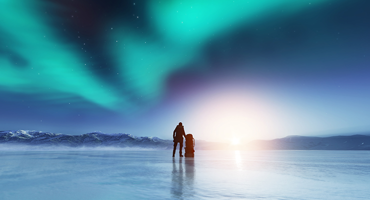 adventurous man standing with a backpack looking northern lights